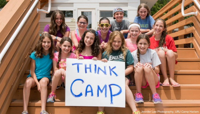 Campers siting on cabin steps holding a THINK CAMP sign