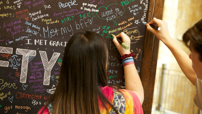 Two teens writing on a chalkboard about what NFTY means to them