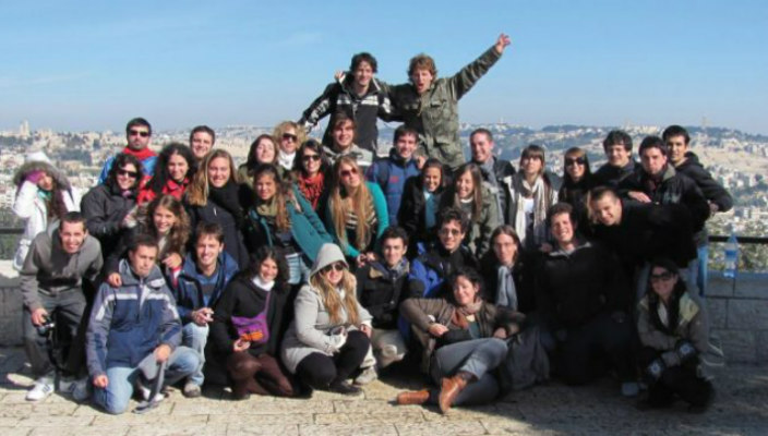 Group of smiling young adults on an overlook in Israel with the Jerusalem skyline behind them
