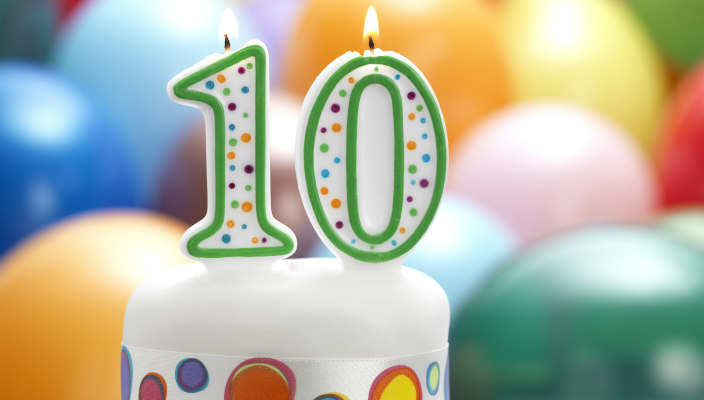 Colorful candles shaped like the number 10 lit atop a birthday cake