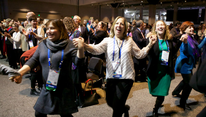 Women laughing as they hold hands and dance around the plenary room during a URJ Biennial song session