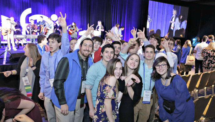 Large group of happy NFTY teens posing in front of the stage where a band is playing