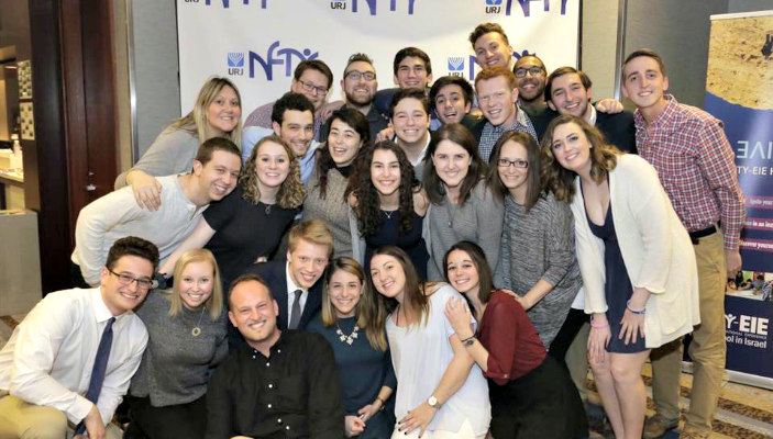 Smiling NFTY members and alumni of all ages pose together in front of a logo banner