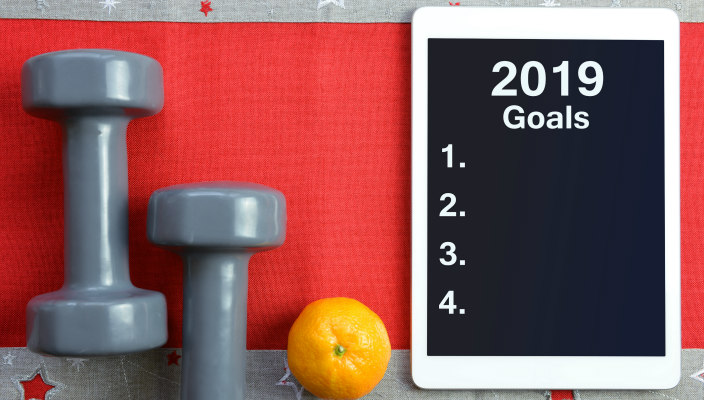 Arrangement of hand weights, an orange, and a small chalkboard to record 2019 goals