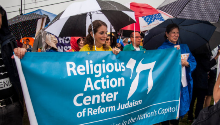 Activists marching in a rally and holding a Religious Action Center banner