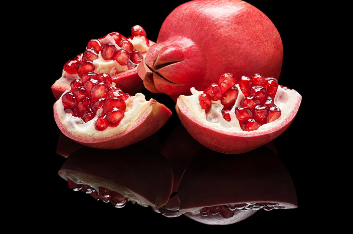 Two pomegranates sitting on a black reflective surface with their mirror images shown below
