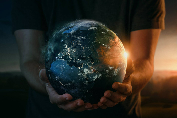 Hands holding a glowing planet Earth
