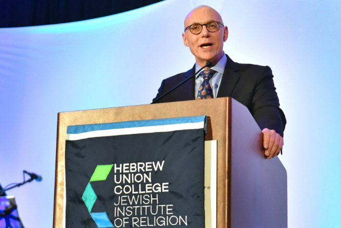 Dr Andrew Rehfeld speaks from a podium with the Hebrew Union College logo on the front