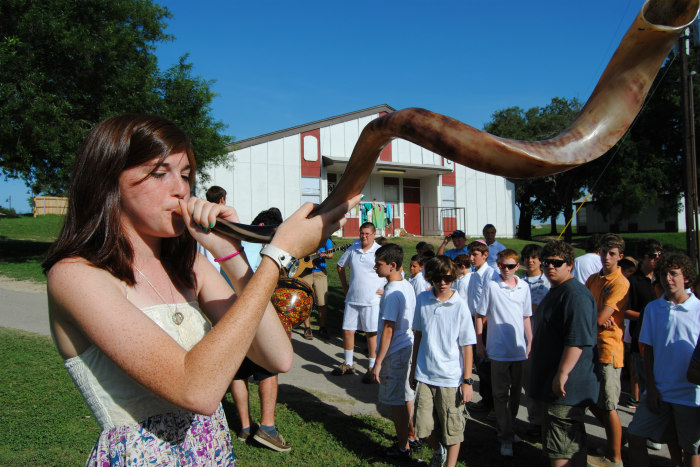 Teen girl blowing a shofar while a group looks on in front of a large outdoor structure as if at summer camp