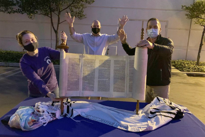 Three masked individuals holding up an unrolled Torah scroll on a table set outdoors