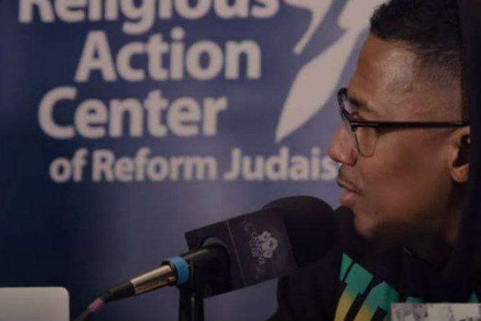 Nick Cannon speaks into a microphone in front of a Religious Action Center banner