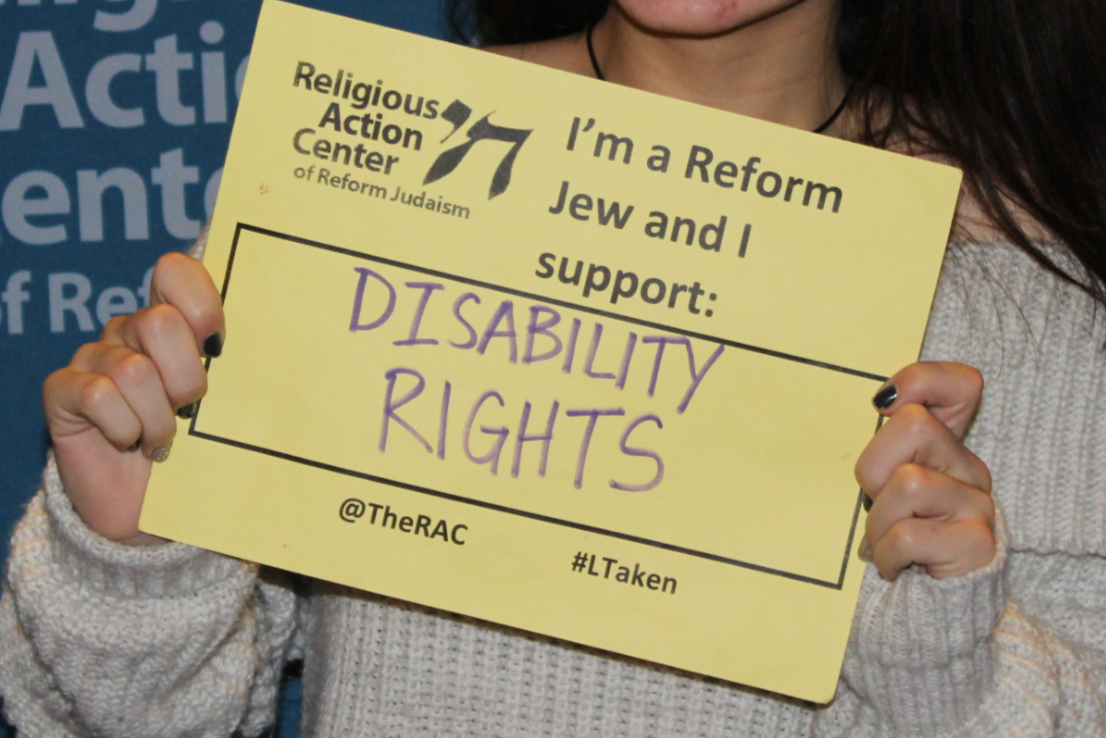 Hands holding a sign reading I AM A REFORM JEW AND I SUPPORT DISABILITY RIGHTS