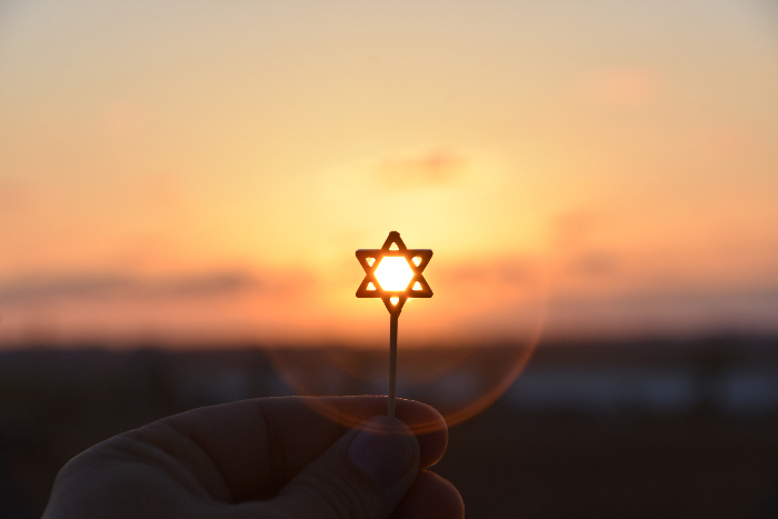 Small Star of David held up against a sunset