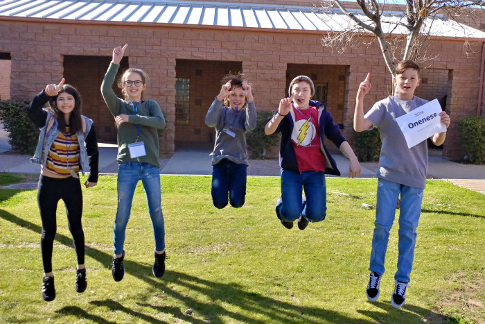 Five smiling teenagers jumping in unison