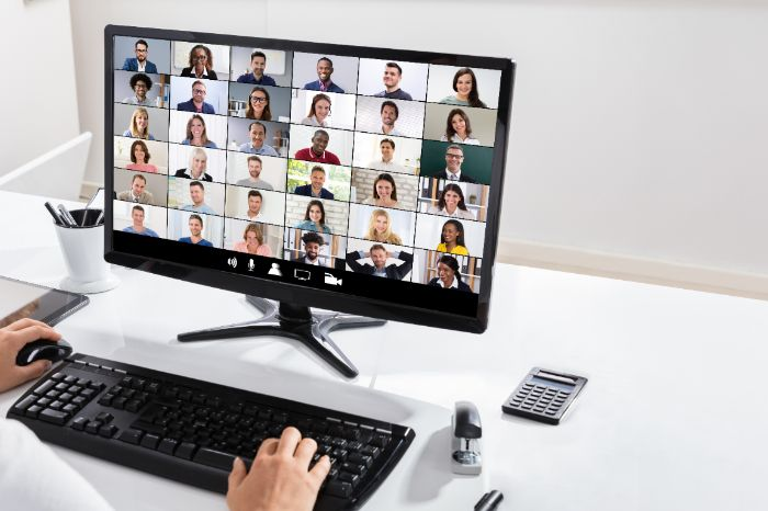 Hands on a keyboard in front of a Zoom screen with a class full of people