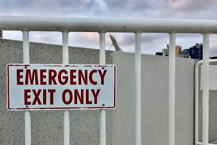 White railing with an EMERGENCY EXIT ONLY sign in red