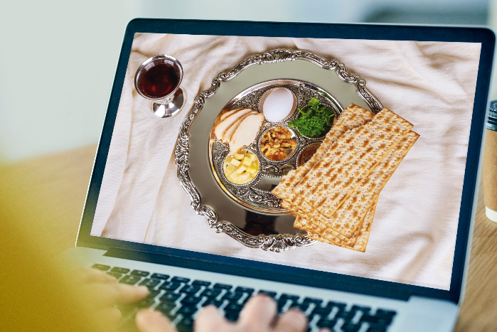 Hands on a keyboard with a seder plate on the computer screen