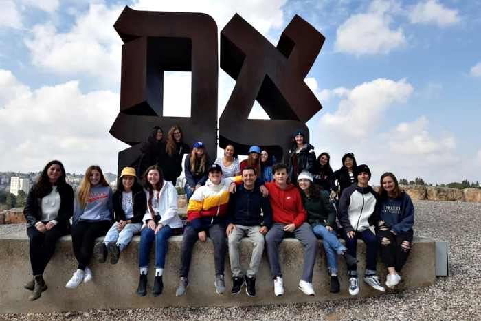 Group of teenage participants in URJ Heller High pose together in front of ahava statue in Israel