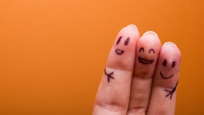 Three fingers with smiling faces written on them on an orange background