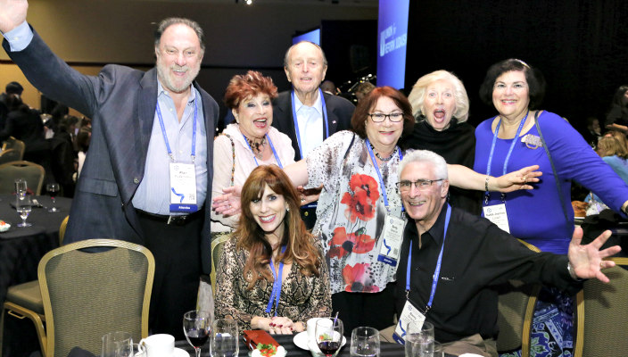 Group of happy people with arms up celebrating at the last URJ Biennial