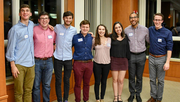 Smiling college students with their arms around one another and nametags on their chests at a campus Shabbat service