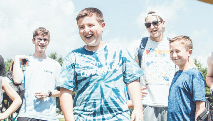 Smiling campers in Camp Harlam shirts looking off camera