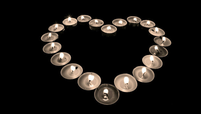 Tealights in the shape of a heart in a dark room