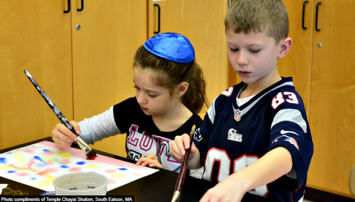 Two children painting together and one of them is wearing a kippah