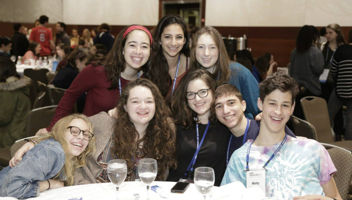 Group of smiling students posing together at a Shabbat dinner table