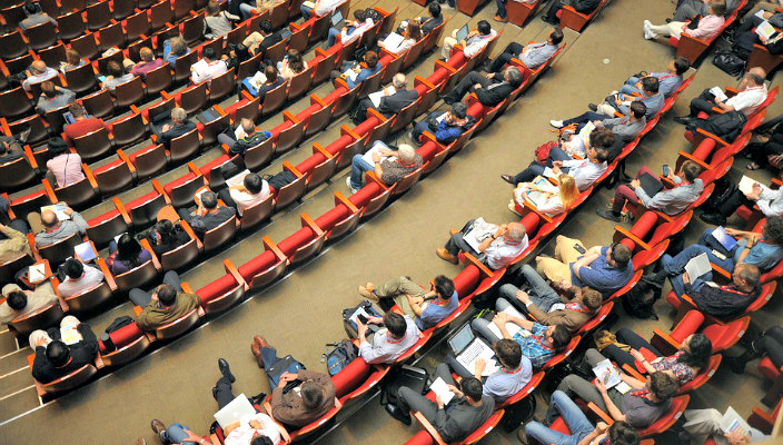 Aerial view of people seated in rows as at a conference or other large event