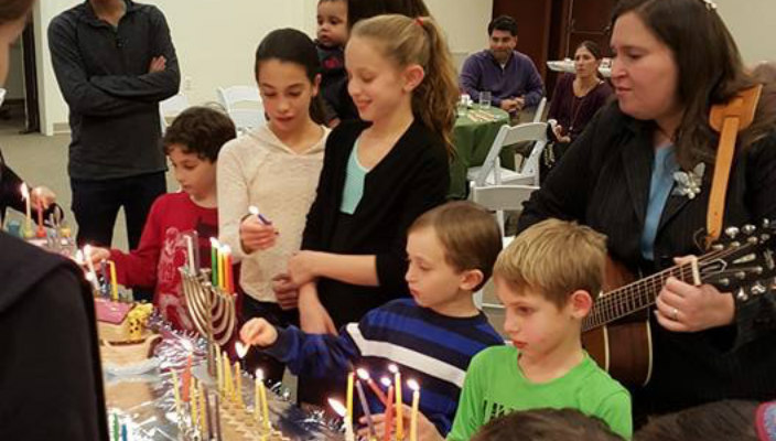 Children light the menorah at a congregational Hanukkah party