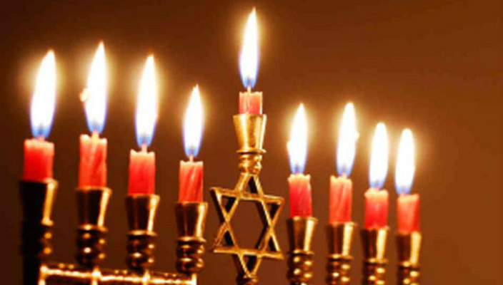 Fully lighted menorah with red candles