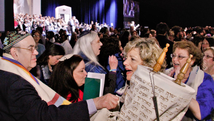 Smiling woman holding the Torah amongst a large crowd at the last URJ Biennial with the event stage visible in the background