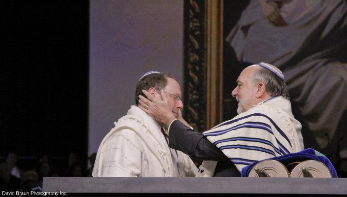 Rabbi David Ellenson holding the face of Rabbi Aaron Panken as he passes on the presidency of Hebrew Union College at Rabbi Pankens 2014 installation