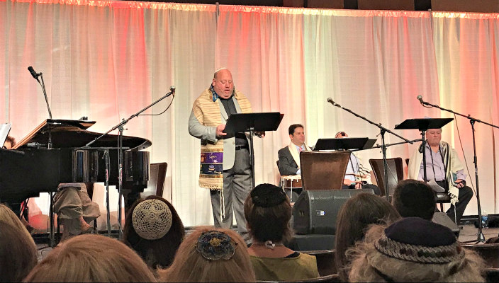 Cantor Steven Weiss stands on a stage to give a dvar Torah before a sea of Jewish musicians wearing kippot and tallitot at a worship service