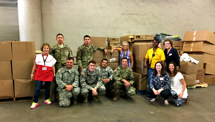 Group of smiling volunteers including some in military uniforms posing with large boxes in a cement warehouse