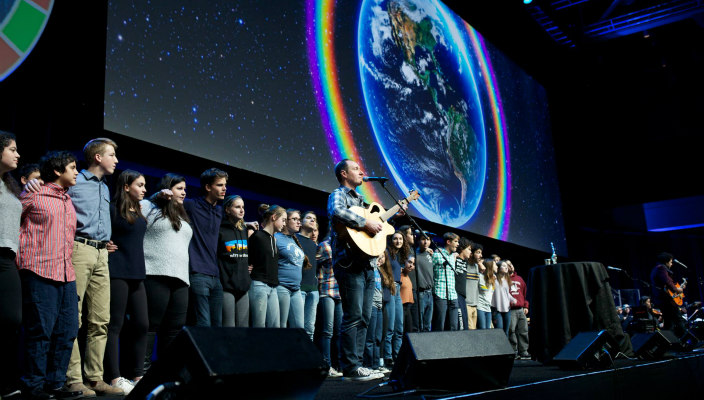 Jewish musician Dan Nichols plays guitar on stage with a line of teens behind him linking arms and a screen depicting the world above them