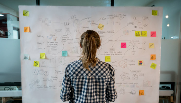 Blond woman facing a flowchart covered in data and PostIt notes