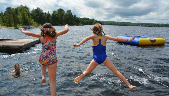 View from behind of two young girls in bathing suits jumping into a lake with a thick forest along the banks