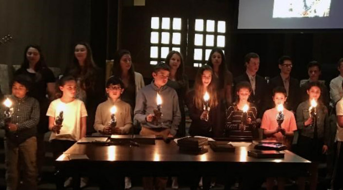 Graduating seniors standing behind fifth graders as they pass candles down to the younger class