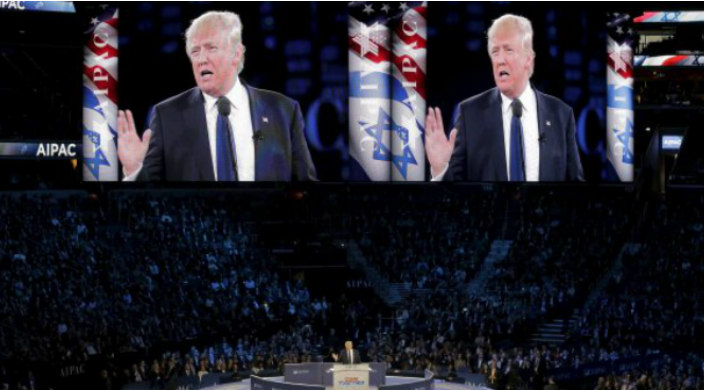 President Trump on stage at the AIPAC Policy Conference with his face shown on large screens about the podium