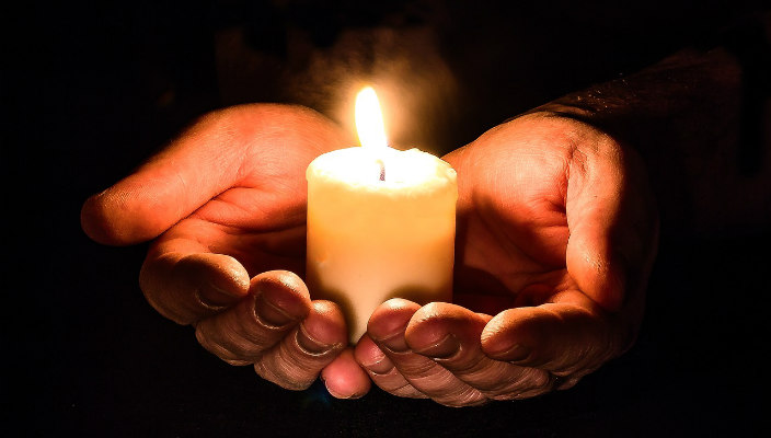 Hand sin the darkness holding a candle