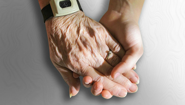 Closeup of and elderly woman and a young woman holding hands as though to represent caretaking