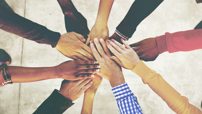 Peoples hands together in a circle as if they are working together or celebrating