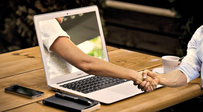 A mans arm reaches out through a computer screen to shake the hand of the man using the computer