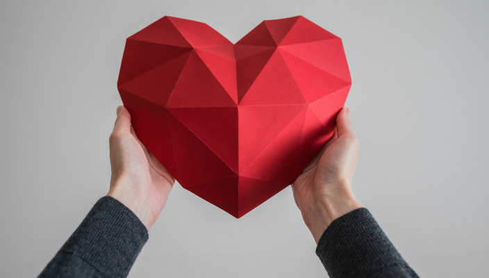 Hands holding a geometric red heart