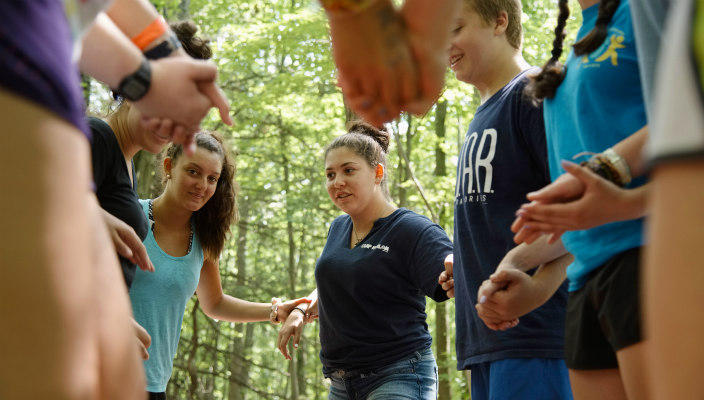 Group of teen campers holding hands in a circle as if participating in a group activity
