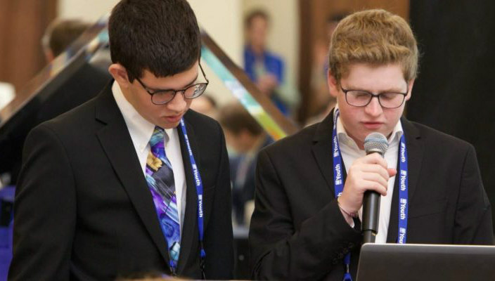 Two teen boys in suits reading from a document in front of a crowd of other teens