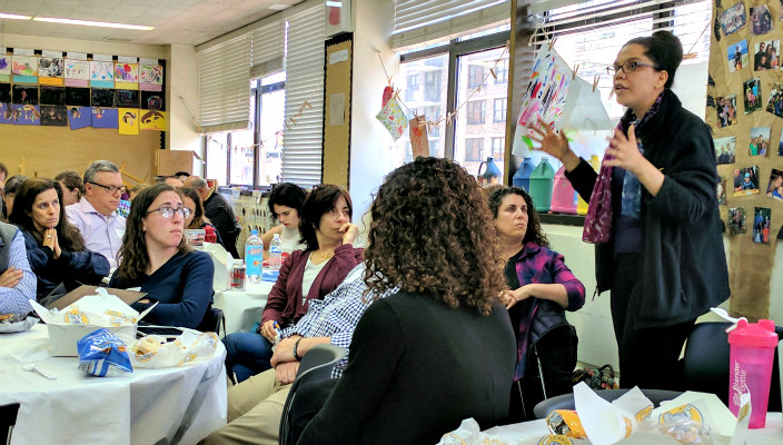 URJ VP of Audacious Hospitality April Baskin stands in a classroom and gestures with her hands as she teaches a room full of participants in the URJ Keshet training partnership
