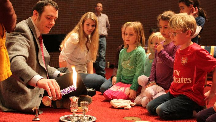 Children sitting in a circle around a rabbi who is lighting a Havdalah candle